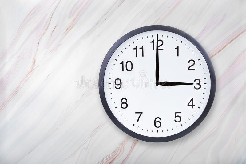 Wall clock show three o`clock on marble texture. Office clock show 3pm or 3am royalty free stock photo