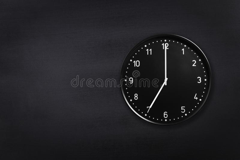 Wall clock showing seven o`clock on black chalkboard background. Office clock showing 7am or 7pm on black texture royalty free stock photo