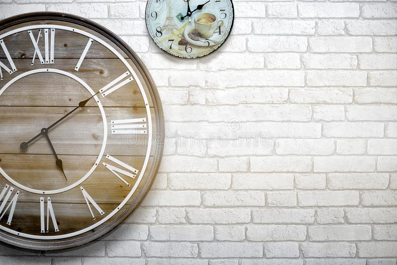 The wall clock vintage is hung on a white brick wall, telling the time accurately. The wall clock vintage is hung on a white brick wall, telling the time stock photos