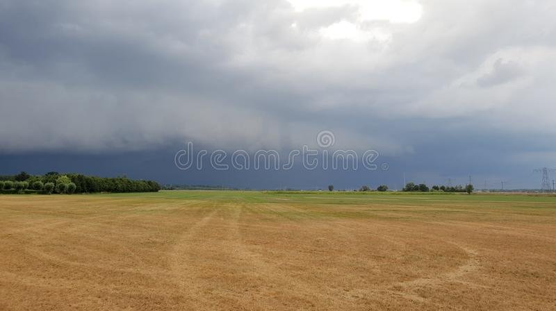 Wall cloud of a thunderstorm above dry yellow fields and green trees in Laag Zuthem in Overijssel, the Netherlands. stock photo