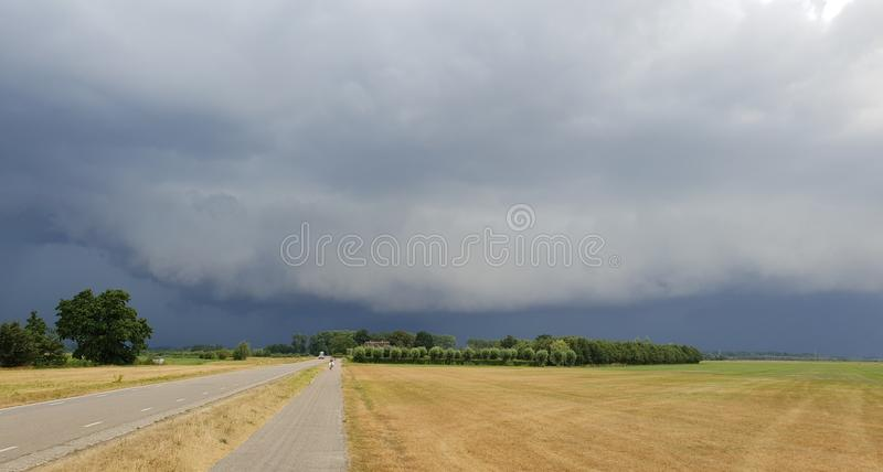 Wall cloud of a thunderstorm above dry yellow fields and green trees in Laag Zuthem in Overijssel, the Netherlands. stock images
