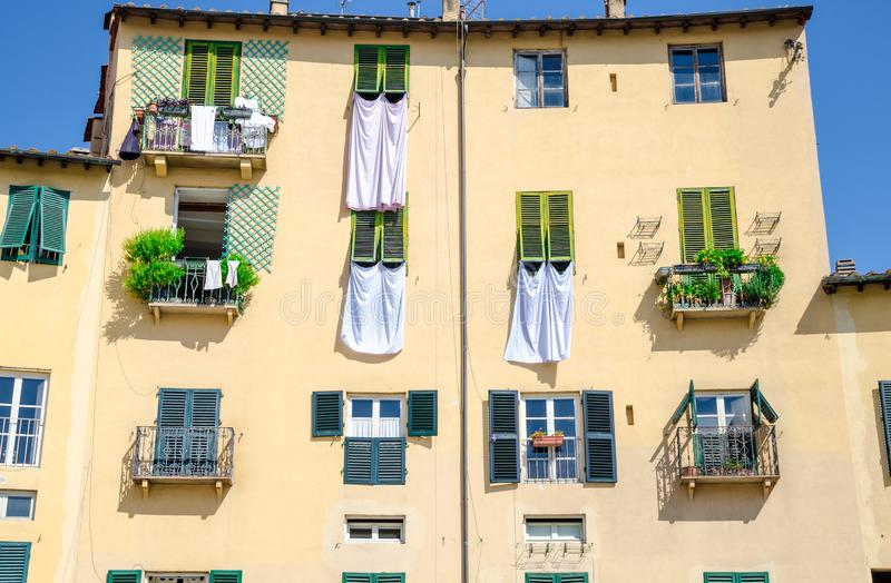 Wall of colorful buildings with shutter windows and drying bed linen on Piazza dell Anfiteatro square of old medieval town Lucca stock images