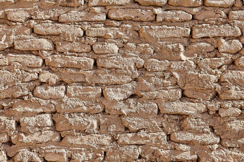 Wall consisting of coarse bricks from clay, sandstone, or lime. Wall fence of formless clay bricks, background texture stock images