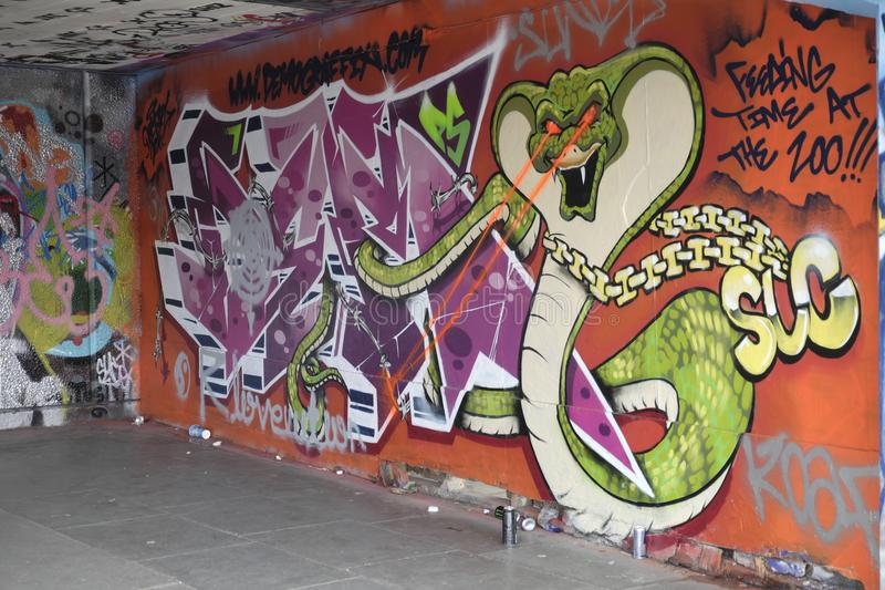 Wall covered with colourful graffiti,London,UK. A wall of the Undercroft skate park in London, with graffiti depicting a giant snake stock image
