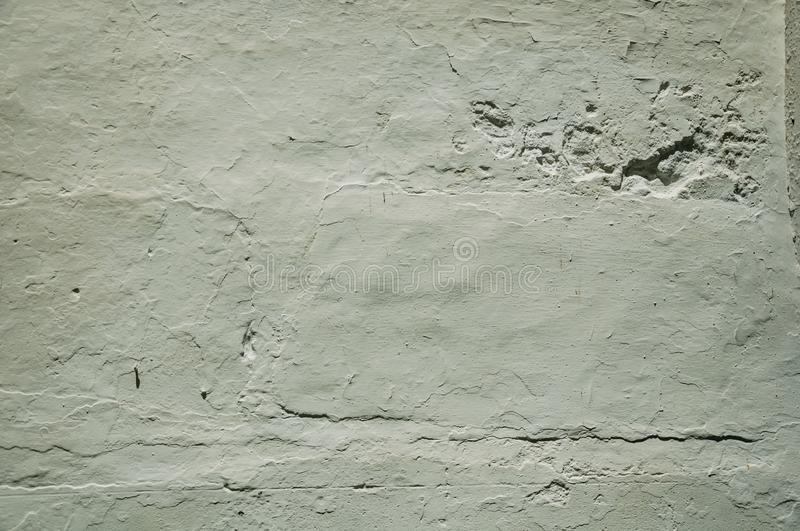 Wall covered by rough plaster with some cracks and chipped royalty free stock photo