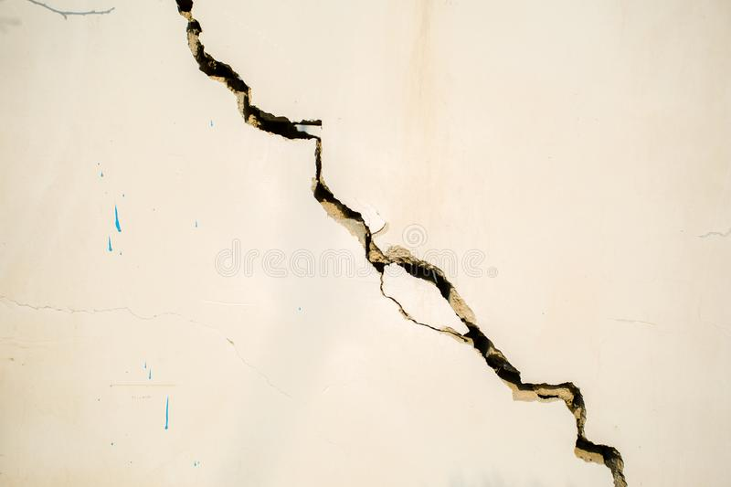 Wall cracks. White wall with cracks in the middle and lateral stock photo