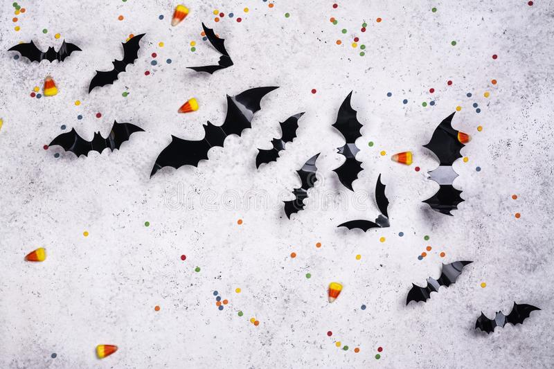 Black paper bats on a stone wall. Wall decor for Halloween - paper bats, sprinkles and candy corns on stone background. Copy space royalty free stock image