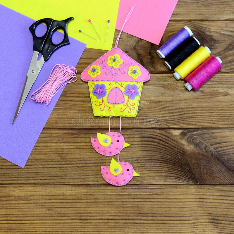 Wall decoration made from felt. Colourful house with birds and flowers. Scissors, felt sheets, colored thread, pin on wooden table. Easter wall decoration stock image