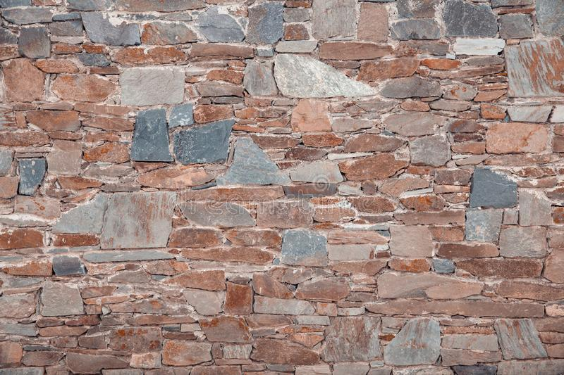 The wall of different colored natural stones forms a mosaic and a background stock image
