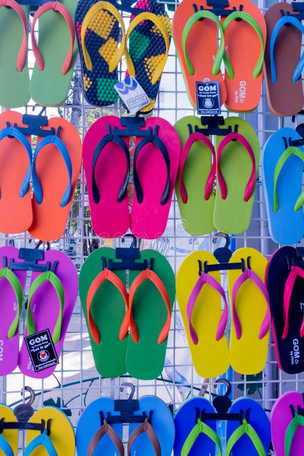 A wall display of colourful flip flops for sale, colours include, green, red and yellow royalty free stock image