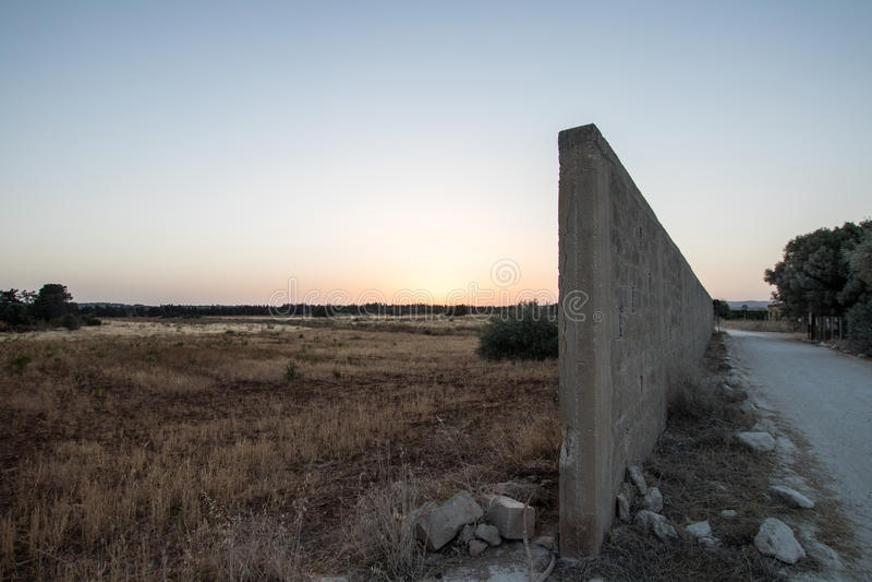 Wall dividing the border. Between a natural summer camp and a white pebble road stock image