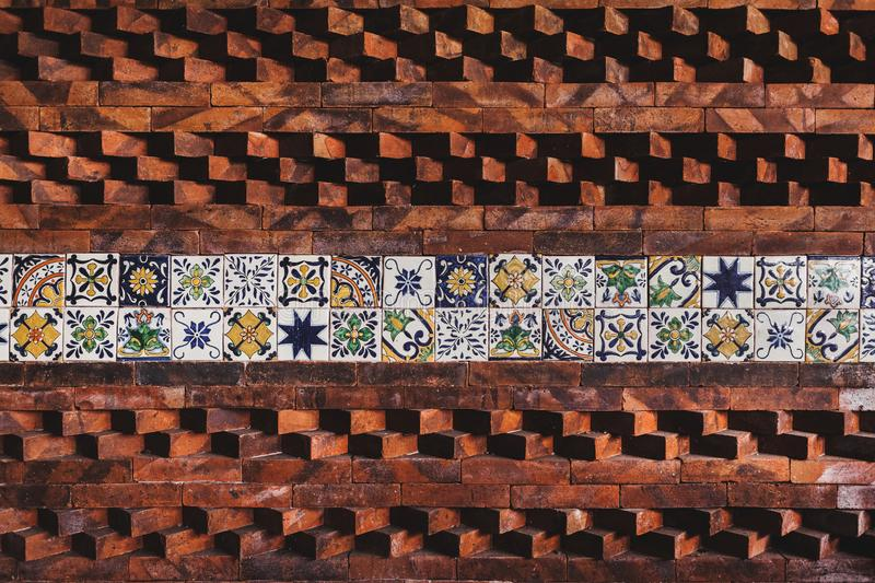 Wall with eastern tile and bricks composition. Wall with eastern ornament tile and bricks composition royalty free stock photo