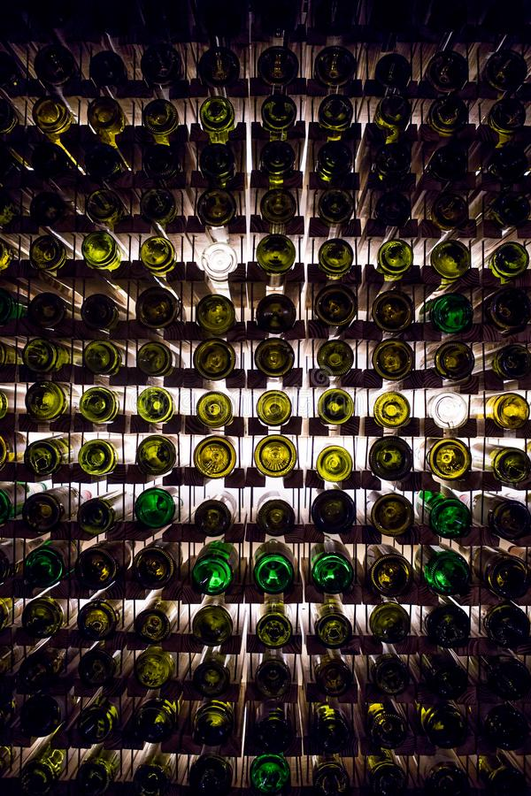 Wall of empty wine bottles. Empty wine bottles stacked-up on one another in pattern lit by the light coming from behind stock photos