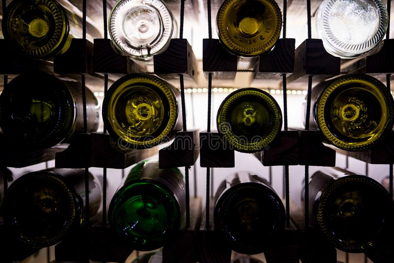 Wall of empty wine bottles. Empty wine bottles stacked-up on one another in pattern lit by the light coming from behind stock image