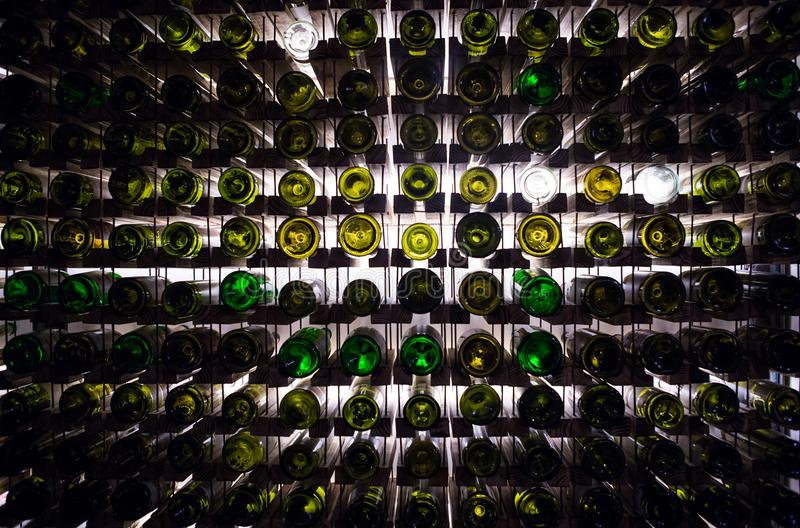 Wall of empty wine bottles. Empty wine bottles stacked-up on one another in pattern lit by the light coming from behind stock photo