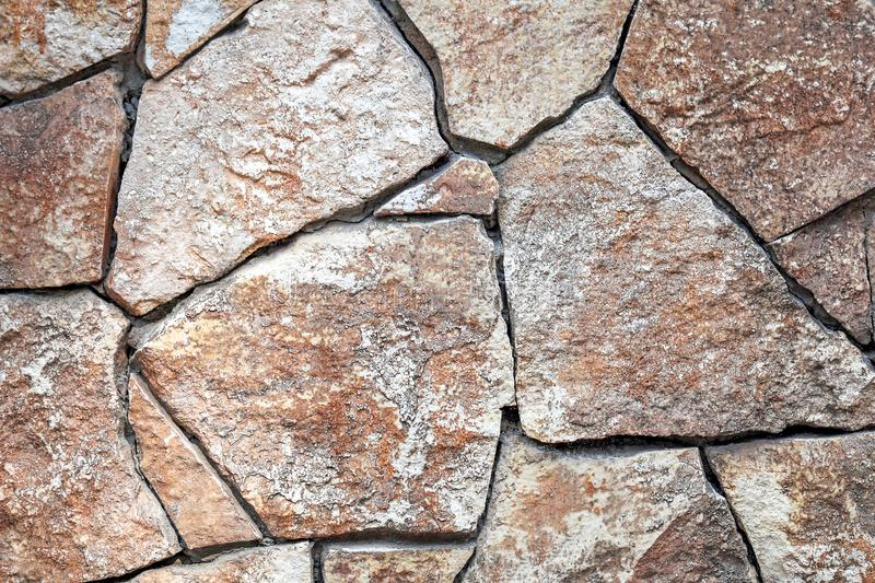 The wall is faced with wild stone of arbitrary shape. Natural brown shades. Background royalty free stock image