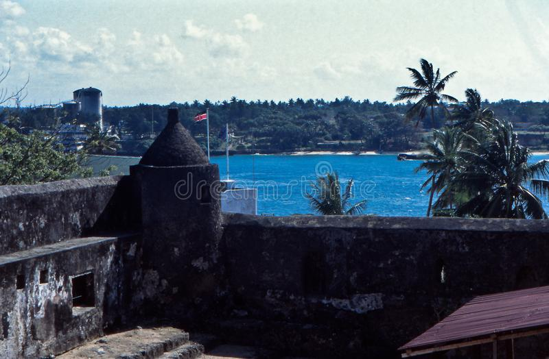 Wall, Fort Jesus, Mombasa, Kenya. Fortification wall of Fort Jesus, Mombasa, Kenya, with view on the Indian Ocean and palm trees royalty free stock images