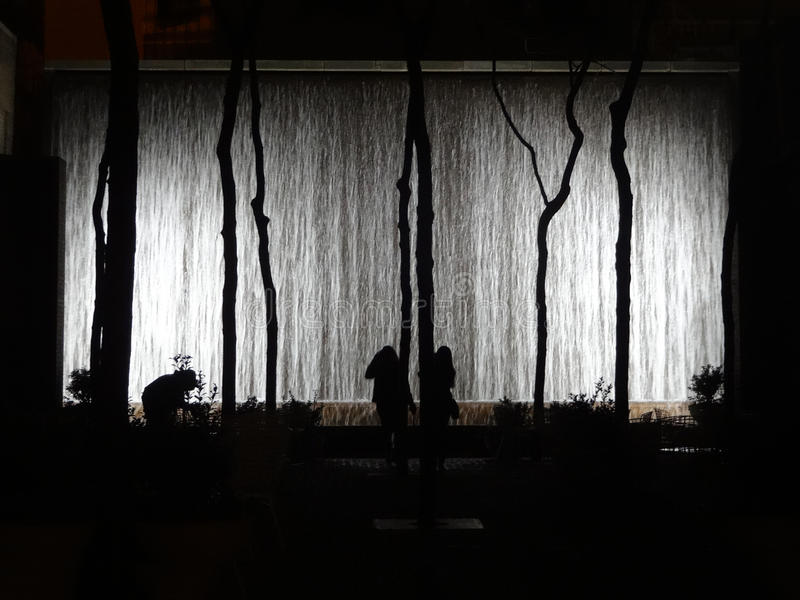 Wall Fountain Glows at Night with Silhouettes in New York City. People stand in front of a wall of falling water at night in New York City stock image
