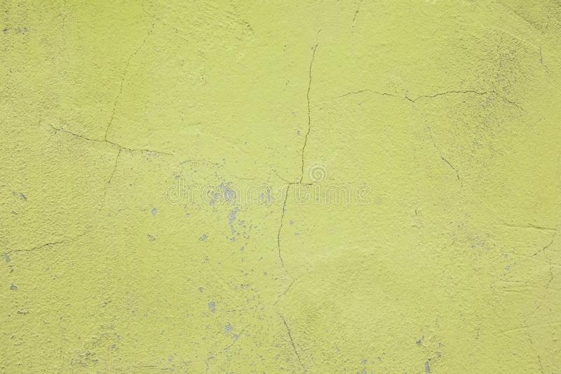 Wall fragment with scratches and cracks. Concrete weathered yellow wall. Vintage texture royalty free stock image