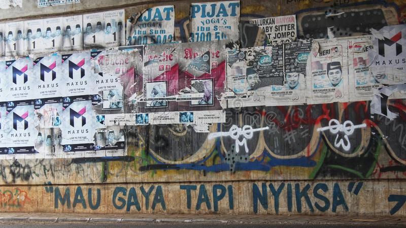 A wall full of grafitti and commercial poster. Vandalism, pylox, paint, glue, street, urban, road, indonesia, jakarta, java, outdoor, day, canon, drawing royalty free stock image