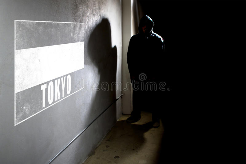 Wall Graffiti And A Hooded Rapper. Hooded hip hop rapper next to wall graffiti with copy space. The concrete wall is in a dark alley stock images