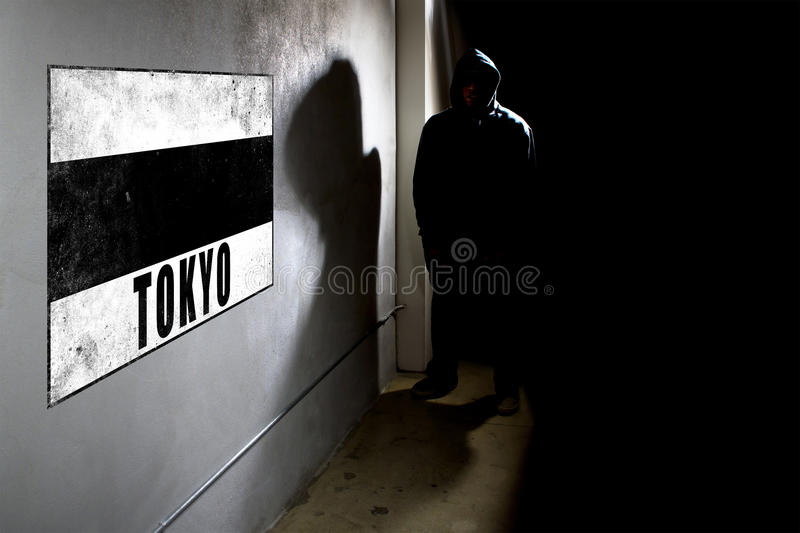 Wall Graffiti And A Hooded Rapper. Hooded hip hop rapper next to wall graffiti with copy space. The concrete wall is in a dark alley royalty free stock photo