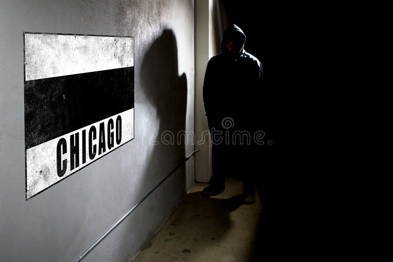 Wall Graffiti And A Hooded Rapper. Hooded hip hop rapper next to wall graffiti with copy space. The concrete wall is in a dark alley royalty free stock photography