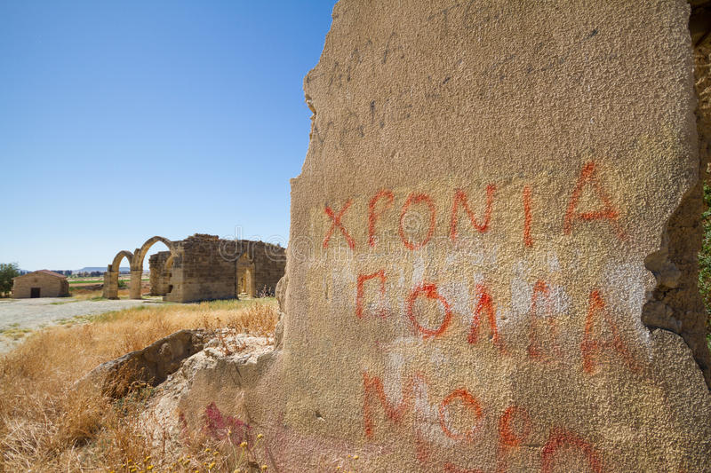 Wall with graffiti and ruins of Saint Mamas gothic church in the background in the abandoned village of Agios Sozomenos, Cyprus royalty free stock photos