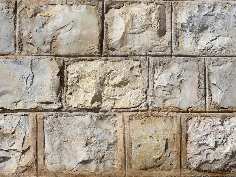 The wall of large stones of yellow tones, reinforced with cement in natural light. stock photography