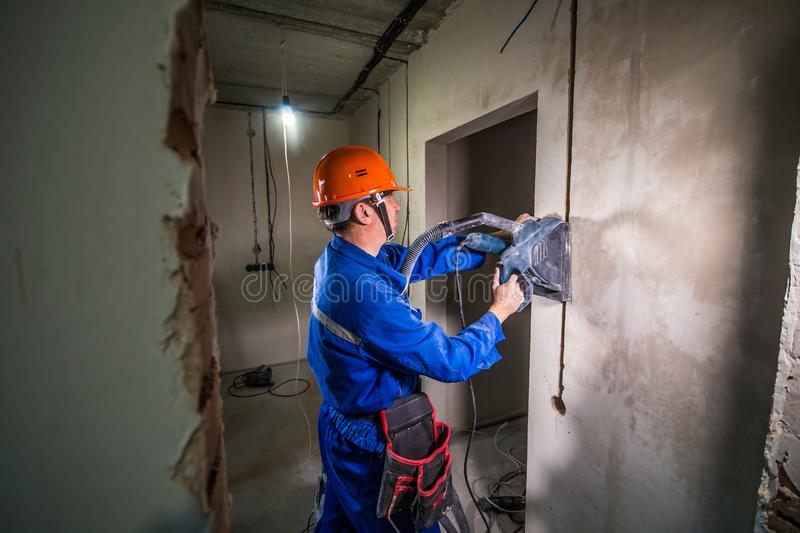 Wall groove cutting machine. Electrician makes a groove in the wall royalty free stock image