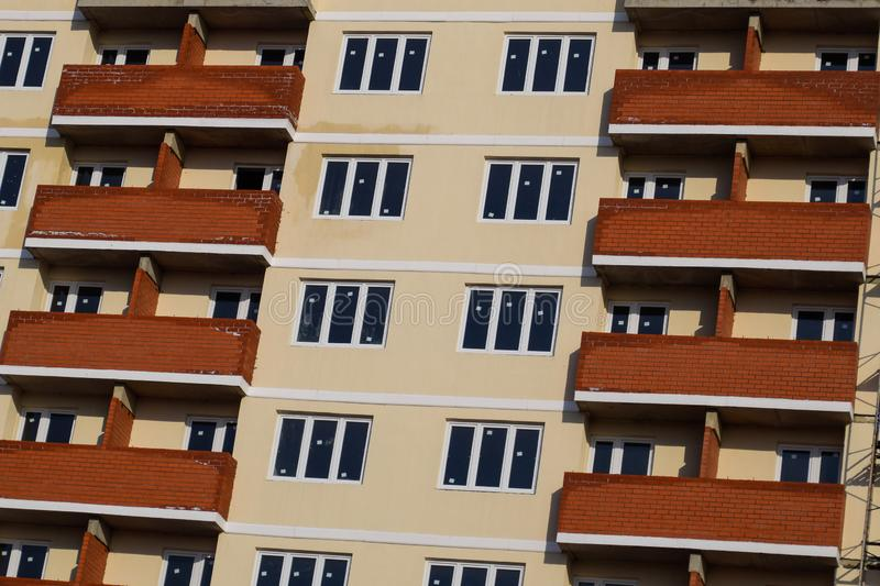 wall of a high-rise brick house, red balconies and yellow walls stock photo