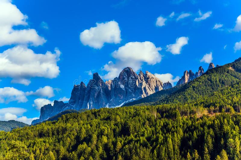 Wall of jagged rocks. In the Val de Funes, Dolomites. Charming green grassy slope of the mountain. Warm autumn day. The concept of ecological tourism royalty free stock photos