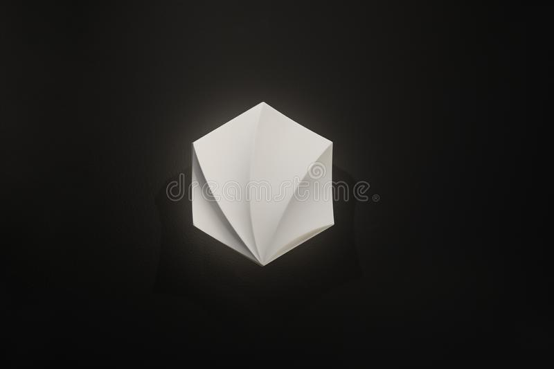 Wall lamp, white with soft light on a black background, interesting shape and made of light material stock photos