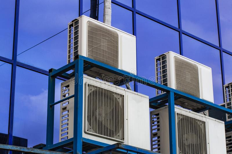 Wall of a large office building with blue windows and air conditioning stock photo