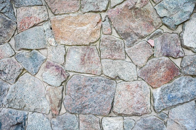 A wall of large rough uneven granite stones with cement grout between them stock photography