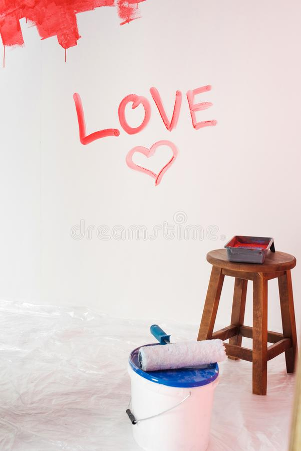 Wall with lettering love and heart symbol, paint tin with paint roller and chair. With roller tray stock photography