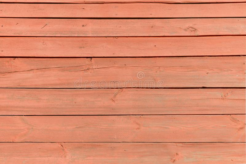 Wall is lined with horizontal wooden slats. Painted in red stock image