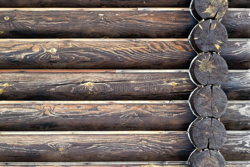 Wall of log house background. Dark brown burnt wooden texture. Copy space. Place for custom text. Horizontal lines with corner logs intersection. Old weathered royalty free stock photo