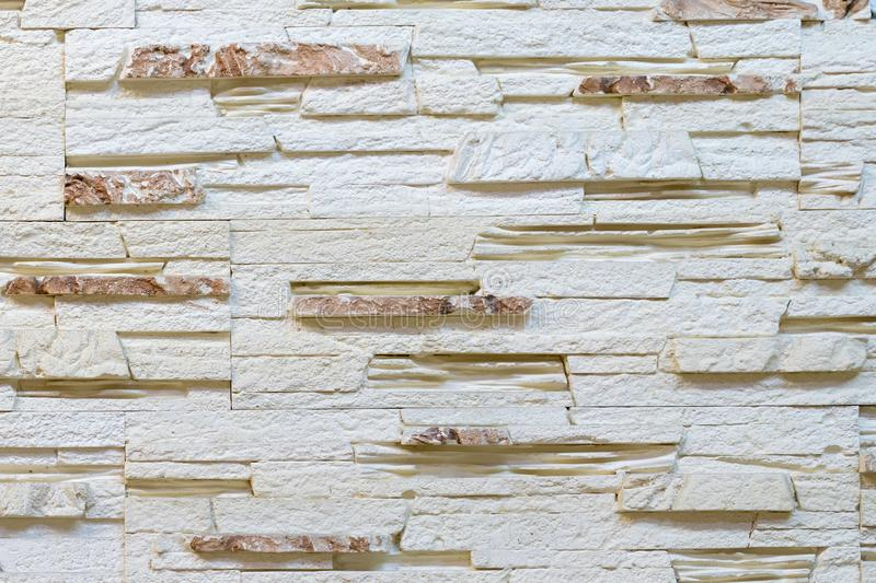 Wall made of decorative light brown stone. Decorating for the fireplace. Background royalty free stock photo