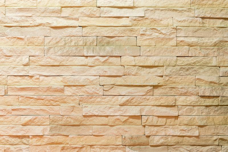 Wall made of decorative light brown stone. Decorating for the fireplace. Background royalty free stock photography