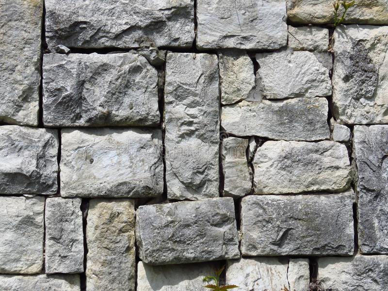 Wall made of grey gray stone blocks. Suitable for background or wallpaper. Brickwork. Stone wall cladding. royalty free stock image