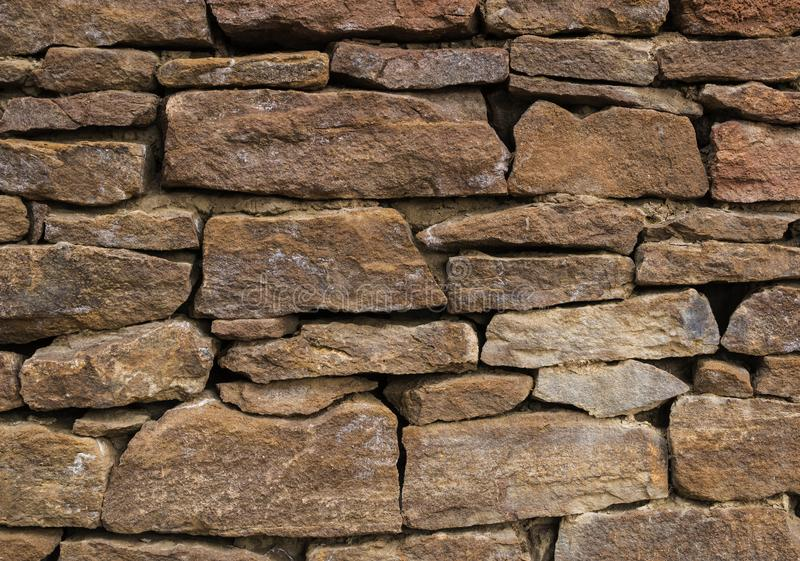 The wall is made of old, ancient stones, with plants growing from seams and cracks. close up. The wall is made of old, ancient stones, with plants growing from royalty free stock photography