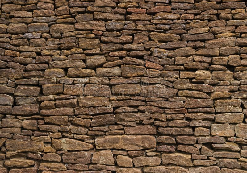 The wall is made of old, ancient stones, with plants growing from seams and cracks. close up. The wall is made of old, ancient stones, with plants growing from stock photography