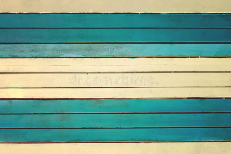 The wall is made of pale yellow and turquoise horizontal slats. Texture of thin painted boards. Blank background stock photos