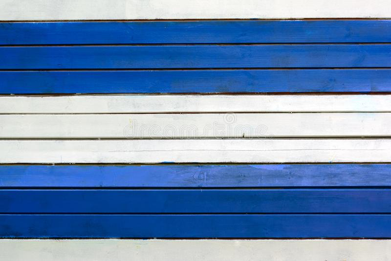 The wall is made of white and blue horizontal slats. Texture of thin painted boards. Blank background stock image