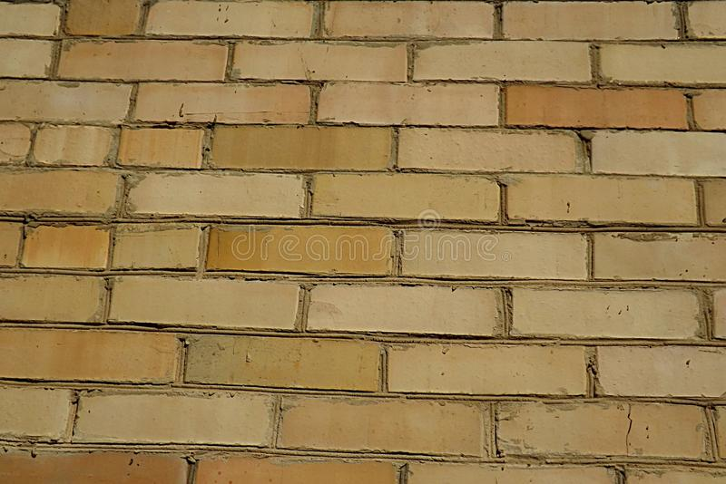 A wall made of yellow brick, capable of serving as a background. The wall is made of yellow tiles of various colors, can be used as a background stock photos