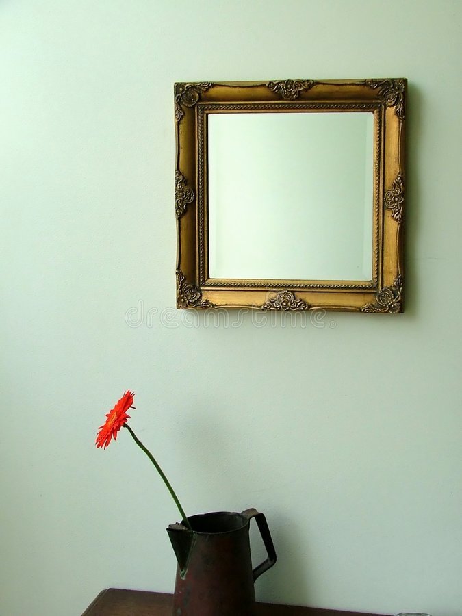 Wall, mirror and red gerbera daisy stock images