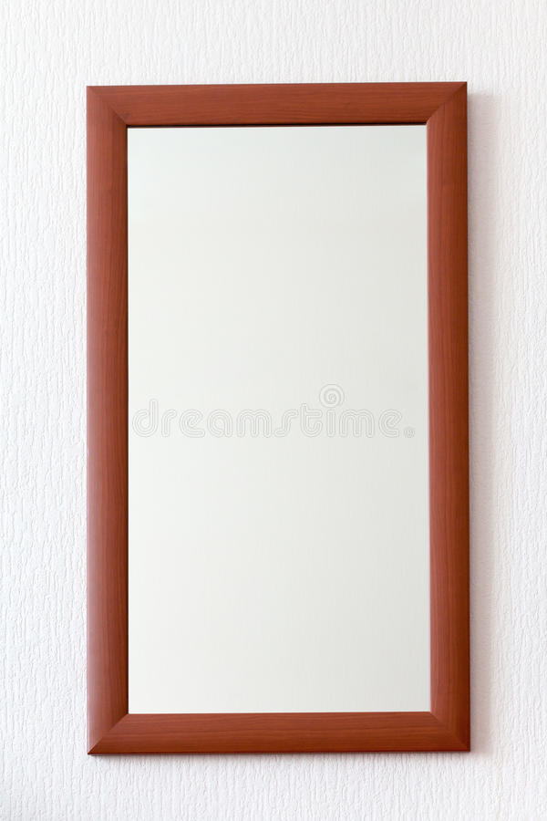 Wall mirror in wooden brown frame. Simple wall mirror in wooden brown frame royalty free stock photography