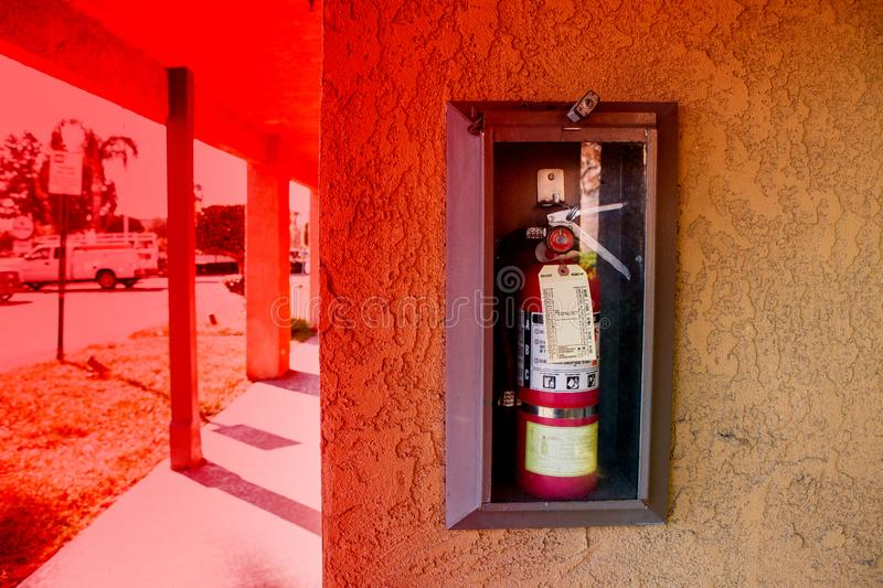 Wall mounted fire extinguisher in an easily accessible glass case. A wall mounted fire extinguisher in an easily accessible glass case stock images