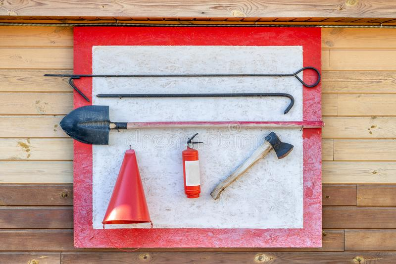 Wall-mounted fire shield with fire-fighting tools. Shovel, hook , axe, cone bucket, fire extinguisher and other equipment hanged. On fire point royalty free stock image